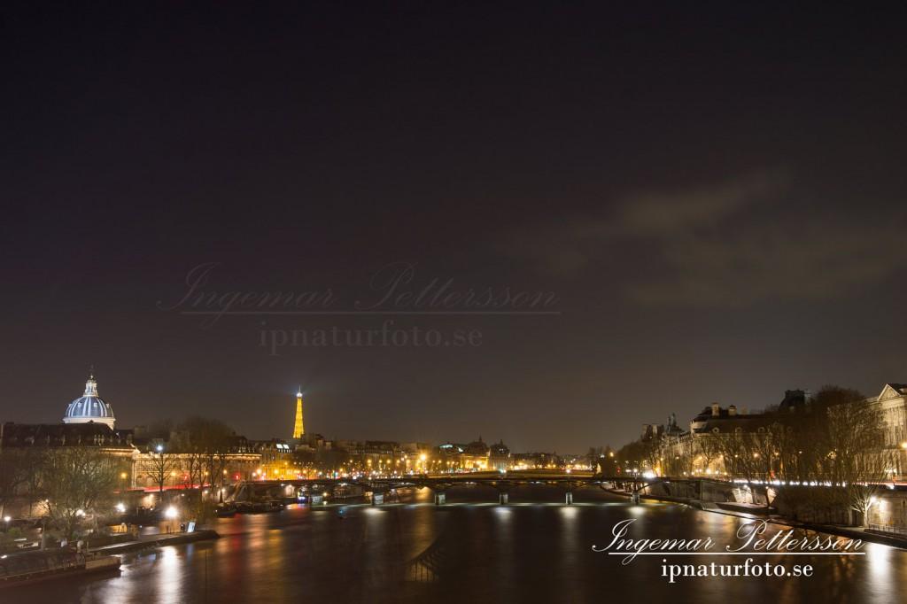 Sakta rinner Seine fram genom vackra Paris en sen natt. och Eiffeltornet skickar sitt sken genom natten.